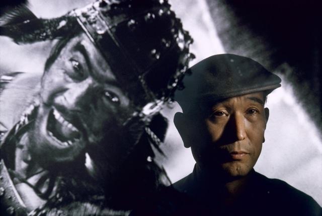, 'Film director Akira Kurosawa standing before an image of his principal star, Toshiro Mifune, Tokyo, Japan,' 1963, Asia Society Hong Kong