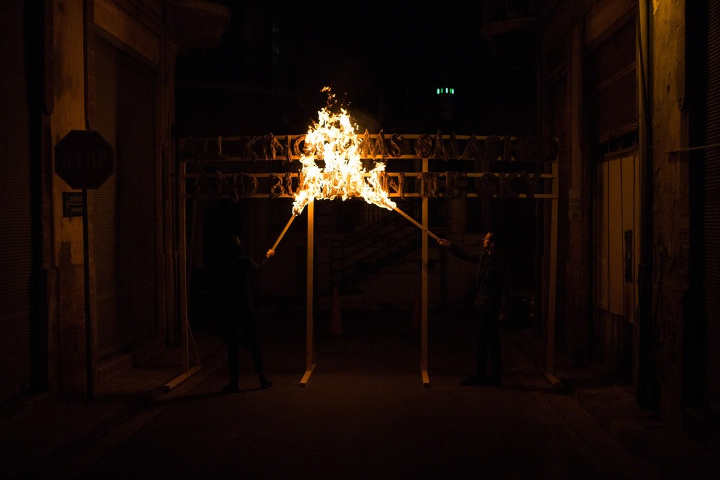 The fire poem was set alight with the Nicosia buffer zone as a backdrop. Photography: Antonis Minas