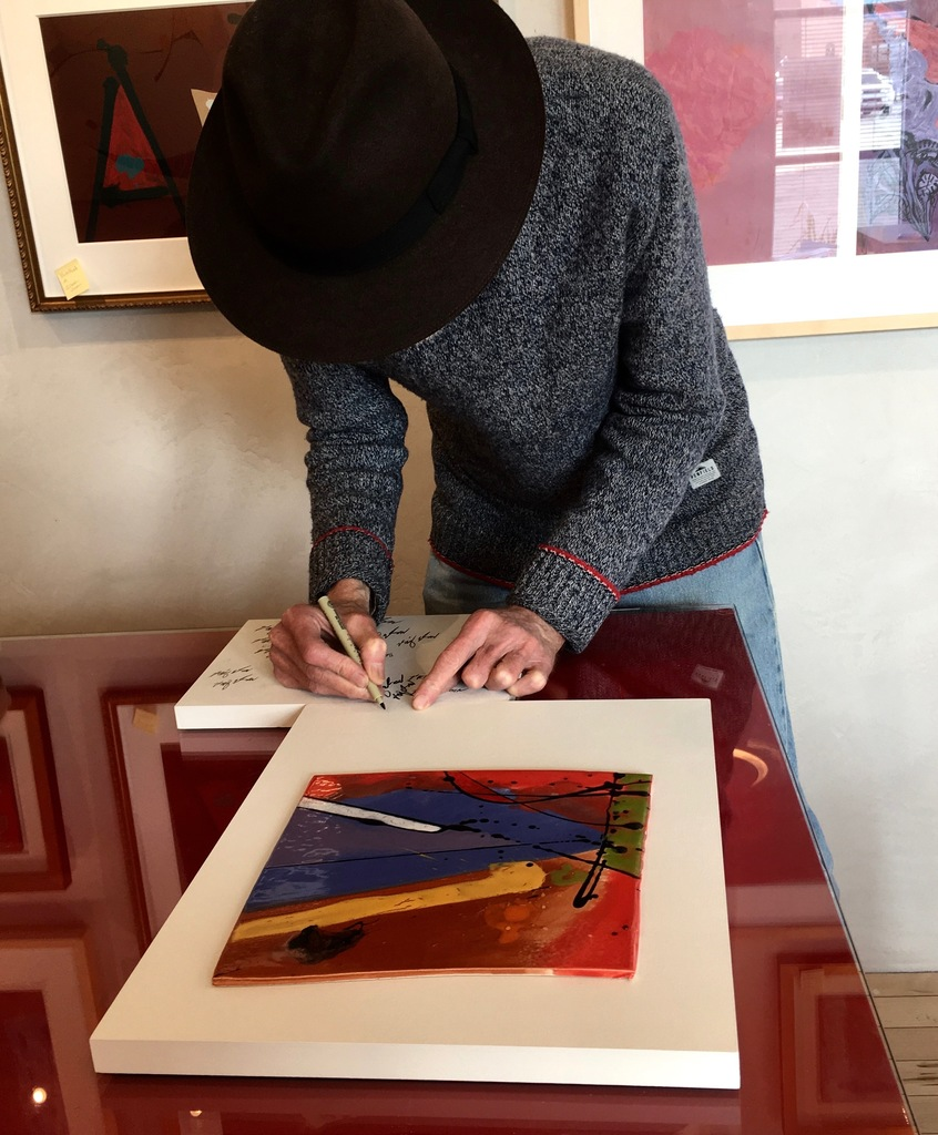 Artist Robert Bigelow signing the small ceramic murals at the gallery on September 20, 2018.