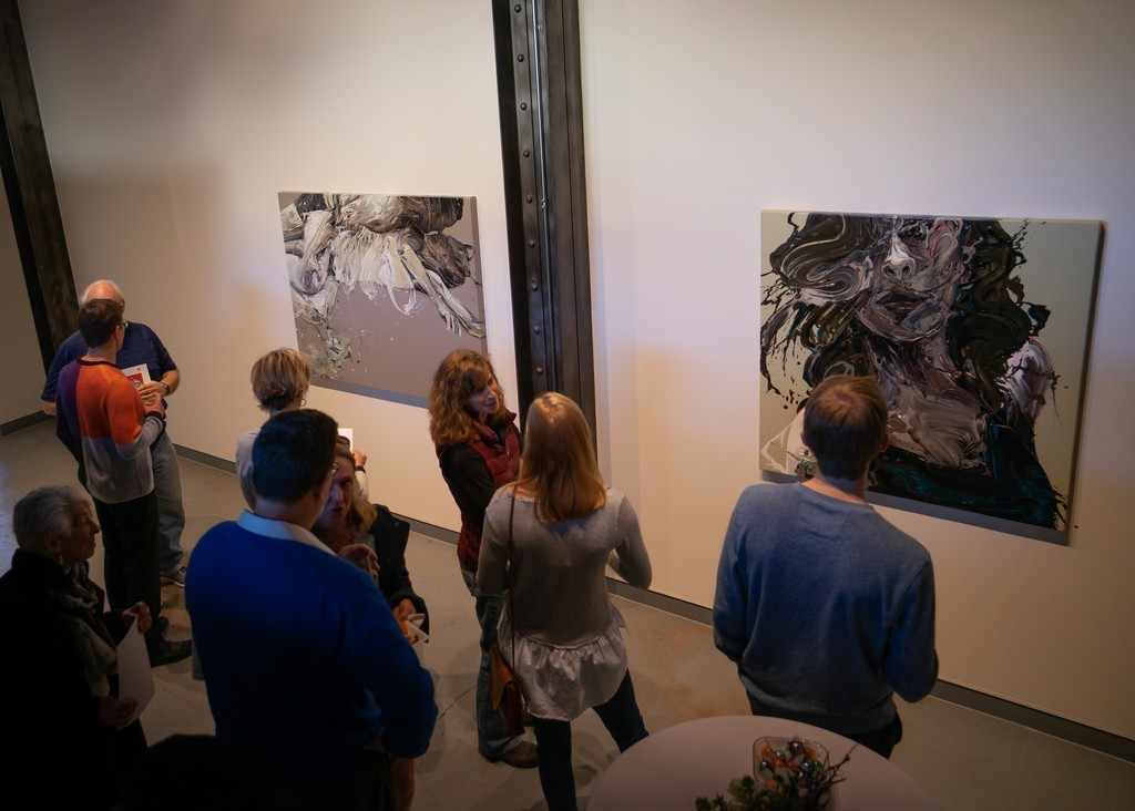 """Visitors at the opening reception; """"Transcription 55 (Linger)"""" (left) and """"Transcription 56 (She)"""" right."""
