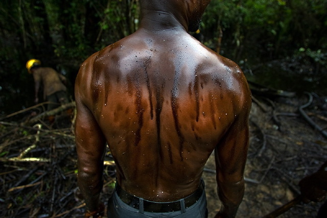 , 'A worker cleans an oil spill from an abandoned Shell Petroleum Development Company well in Oloibiri, Niger Delta, Nigeria,' 2004, Anastasia Photo