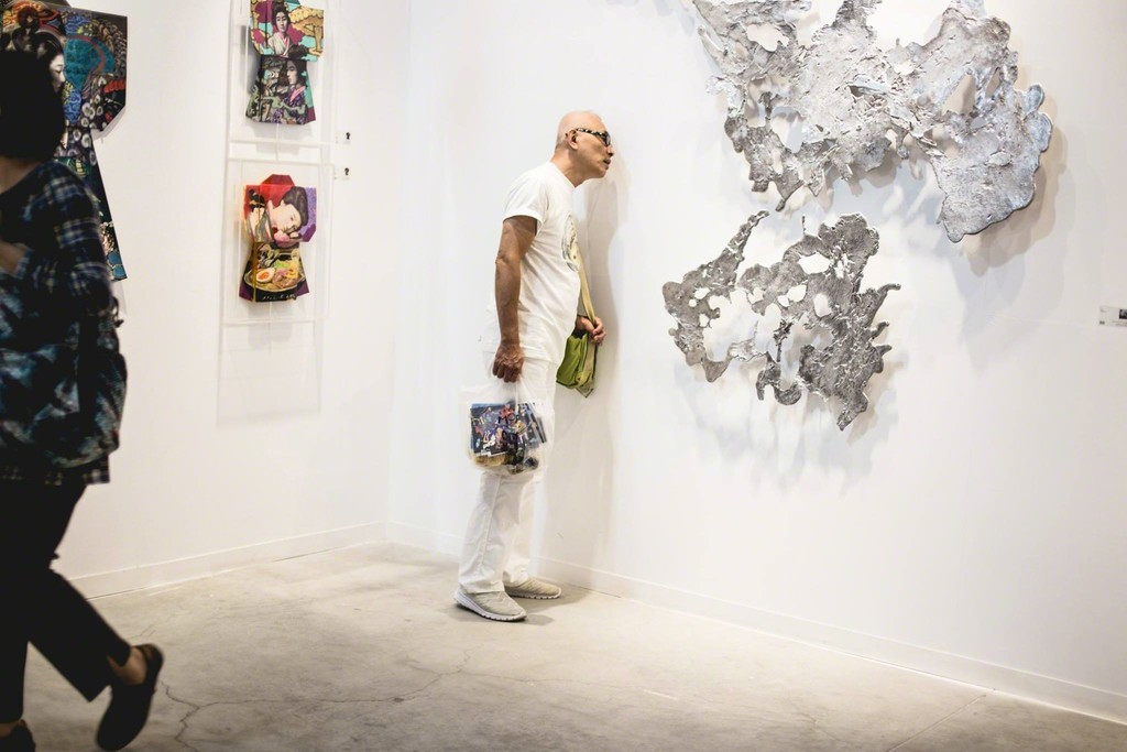 "A visitor examines Jinggoy Buensuceso's melted aluminum piece, ""Ink."""