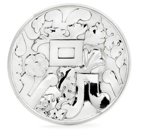 A circular silver dish with stylized ornamentation.