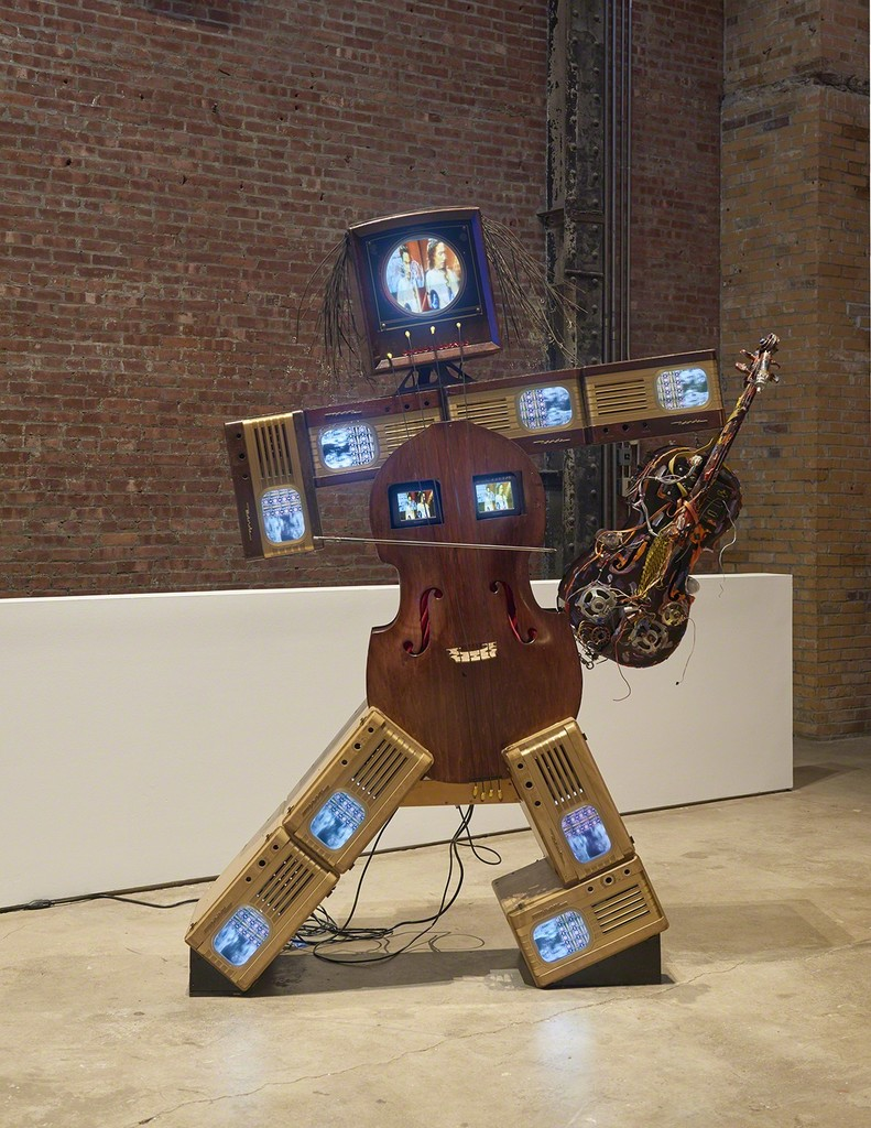 Nam June Paik, Charlotte Moorman II, 1995, installation view. Nine antique TV cabinets, two cellos, one 13-inch color TV, two 5-inch color TVs, eight 9-inch color TVs, and two- channel video. 92 x 68 x 24 inches (233.68 x 172.72 x 60.69 cm). The Rose Art Museum, Brandeis University, Waltham, MA; Hays Acquisition Fund. Photo: Kyle Knodell