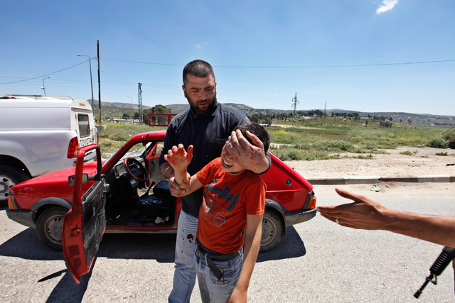 , 'A Palestinian man holds a boy's head after Jewish settlers threw stones at their car, south of Nablus in the West Bank. The settlers threw stones at Palestinians during the funeral procession of Ben Yosef Livnat, a 25 year old shot to death by Palestinian policemen at Joseph's Tomb holy site in Nablus,' 2011, Ronald Feldman Gallery