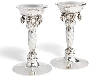 A pair of large sterling silver candlesticks with grapes.