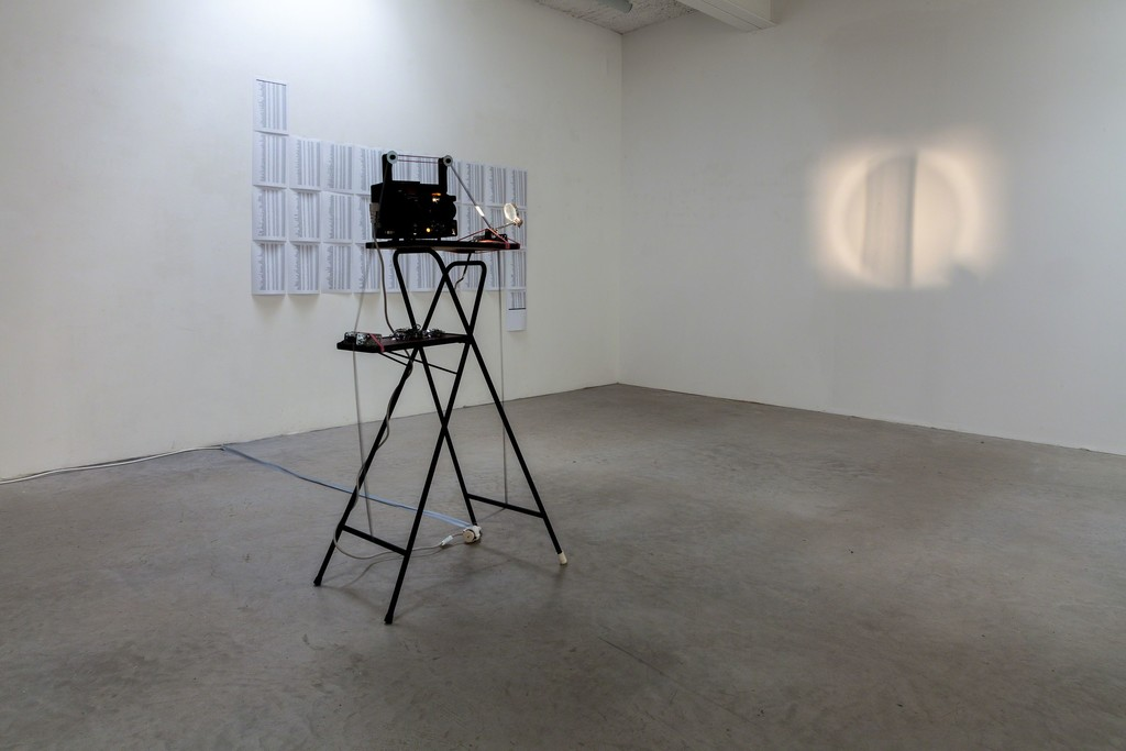 """Jens Standke, exhibition view: (foreground) """"Visual Loops"""", 2016   videotape, Loop, film projector, magnifying glas, rubber bands, projector table and (background) """"2,339 cm/s"""", 2016   s/w laser print on A4 paper, 32 pages, format variable   image: ©dasesszimmer"""