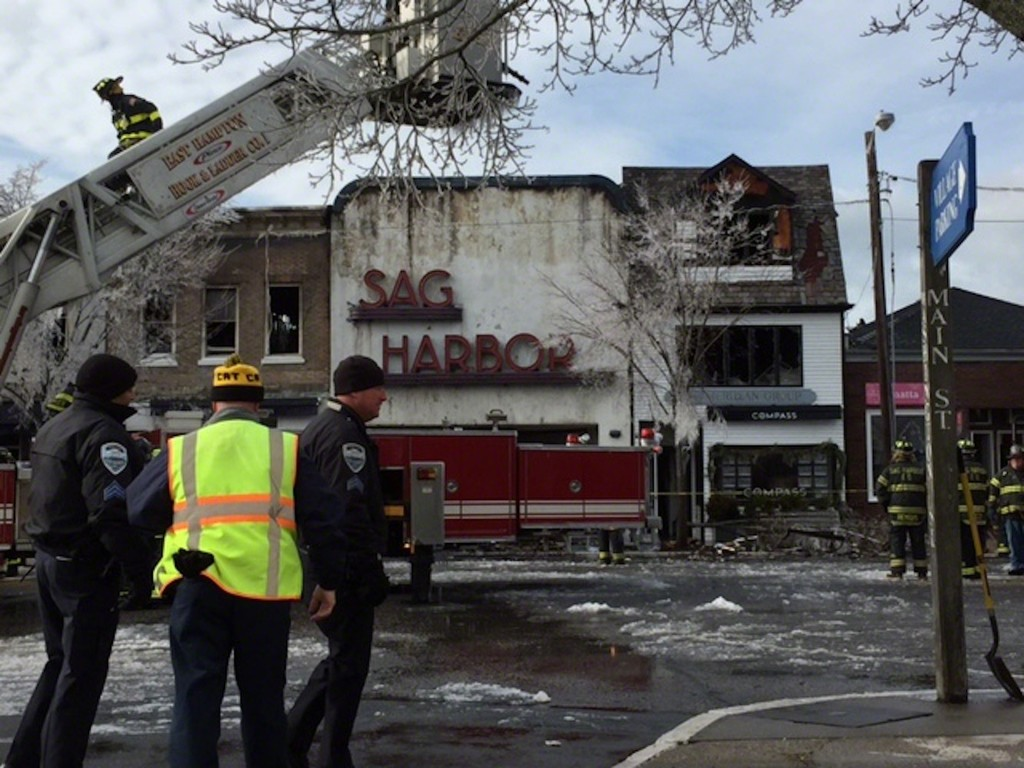 12/16/2016 - Sag Harbor First Responders have finally stopped the fire. A tree in the background is frozen from water from the fire hoses. The burnt cinema facade stands.