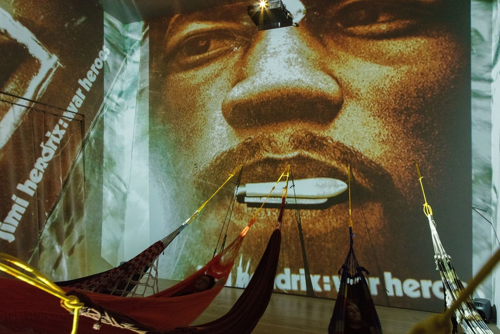 Hélio Oiticica. Installation view. CC5 Hendrix-War,1973.Thirty-three 35mm color slides transferred to digital slideshow, sound, and hammocks. Site Specific Collections of César and Claudio Oiticica and Neville D'Almeida. Whitney Museum of American Art, New York, N.Y. Photograph by Oto Gillen