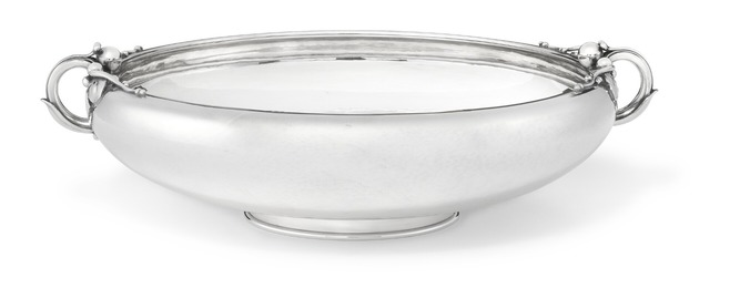 Circular sterling silver fruit dish with hammered surface. Two handles with leaves and berries.