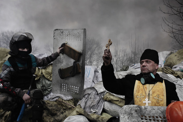 Jerome Sessini, 'An Orthodox priest blesses the protesters on a barricade. Kiev, Ukraine.', 2014, Photography, Magnum Photos