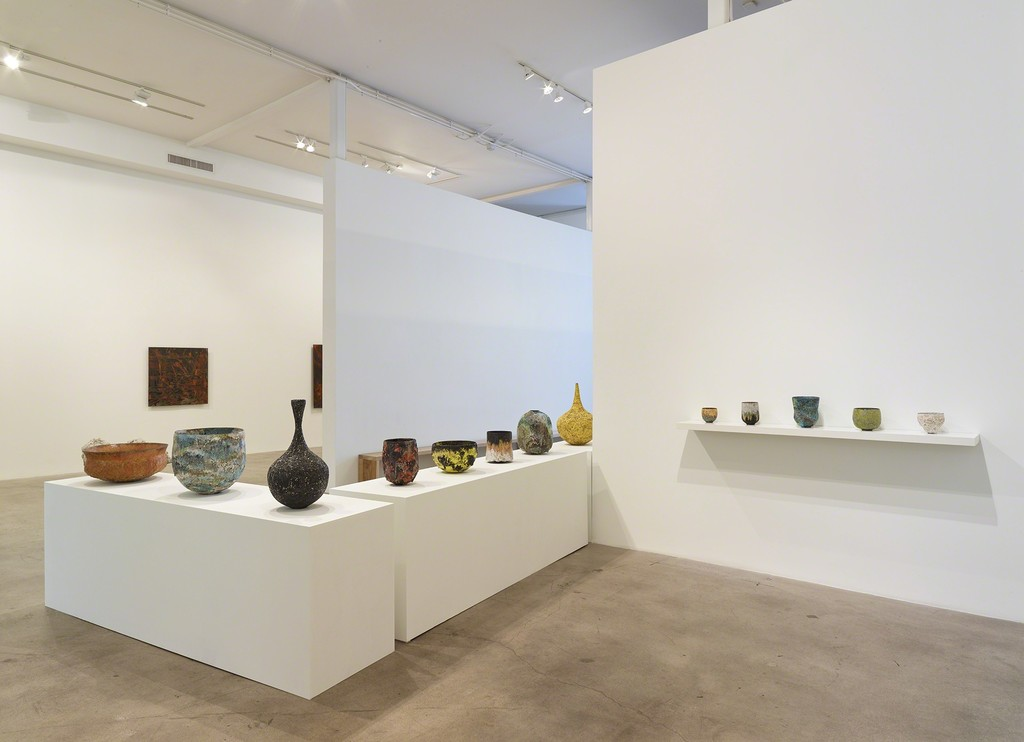 "Installation view of ""Transfigured."" with (left) ceramics by Jay Kvapil, ];  (rear) paintings by Lionel Sabatte´"