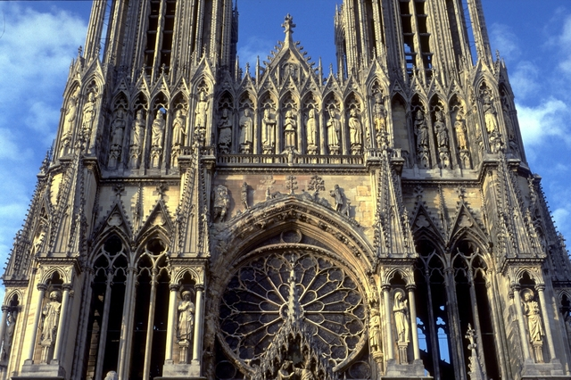 'Reims Cathedral: exterior, detail of West facade showing tracery of West Rose Window and gable over central portal (Coronation of the Virgin)', ca. 1211-1290, Allan Kohl