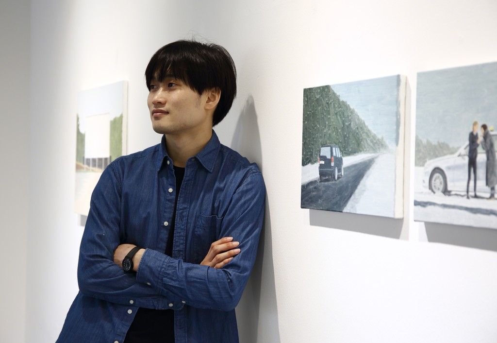 Artist Byungkoo Jeon next to his works
