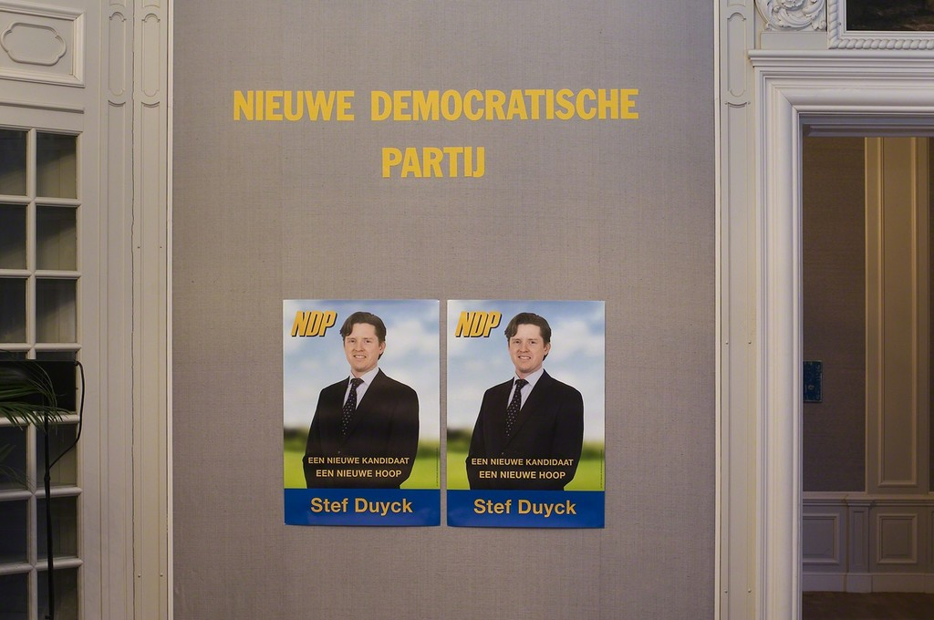 Guillaume Bijl. Nieuwe Demokratische Partij (A New Democratic Party). Installation with chairs, stage, flatscreens, flags, palms, lights, music, curtain, posters, pulpit etc, 2016. 500 x 800 x 1100 cm. Detail