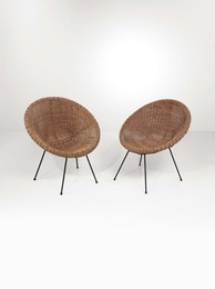 A pair of chairs with a wicker seat and lacquered metal structure