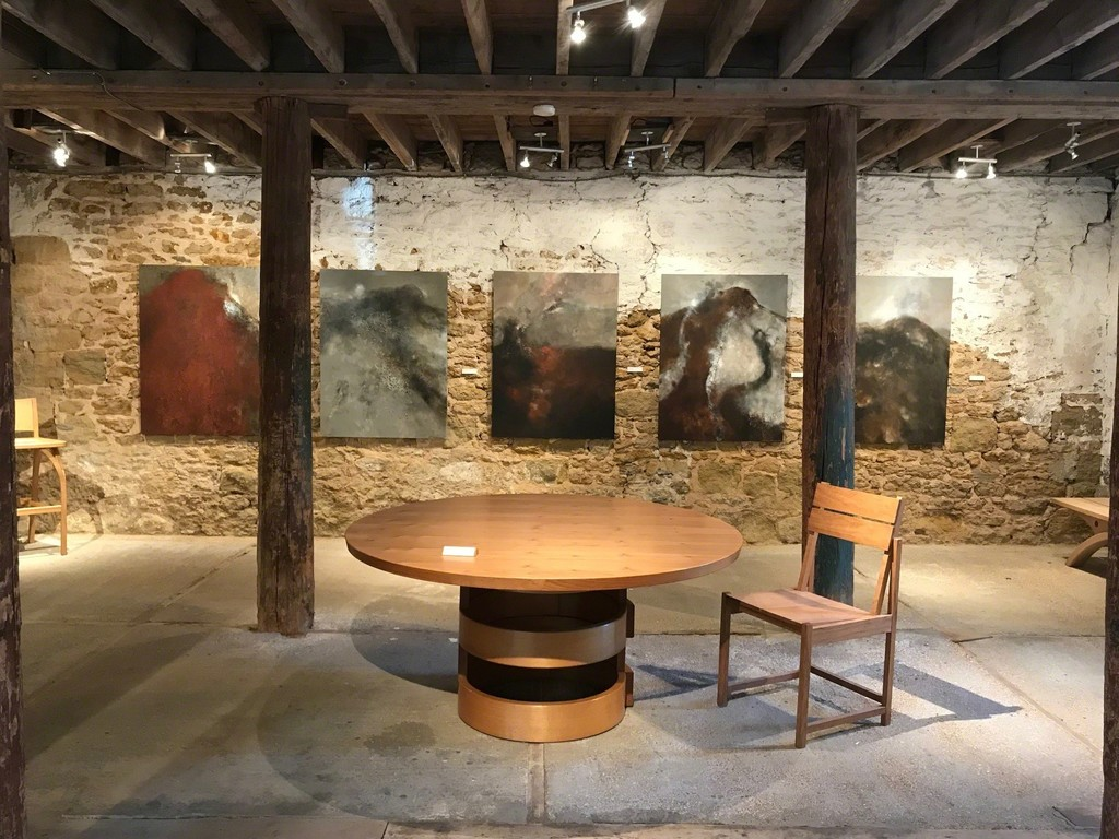 Petter Southall's Three and Two Half Rings Table and Bauhaus Chair with five Brian Graham paintings on the walls.