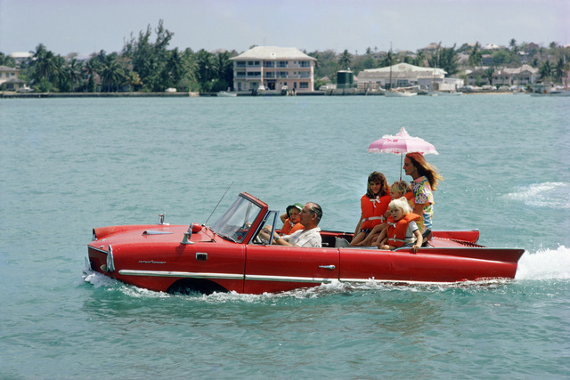 ", 'Sea Drive, 1967: Film producer Kevin McClory takes his wife Bobo Segrist and their family for a drive in an ""Amphicar"" across the harbour at Nassau, Bahamas,' 1967, Staley-Wise Gallery"
