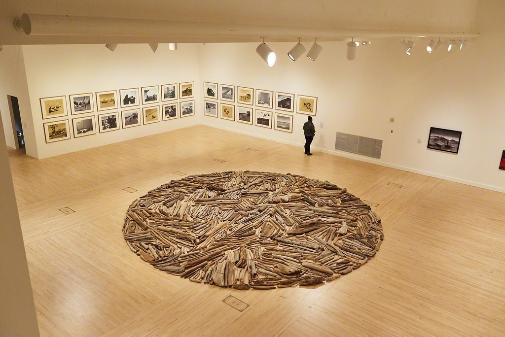 "A guest observing ""Up in the Sky,"" a 1997 work by Tracey Moffatt. Richard Long's 1996 piece ""Puget Sound Driftwood Circle"" is in the foreground.