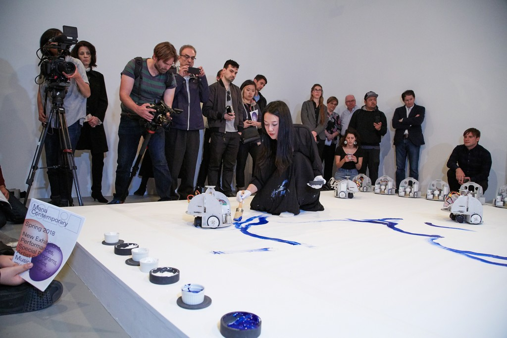 "Sougwen Chung's performance of ""Omnia per Omnia,""April 29, 2018, part of ""Only Human"" April 29–June 2, 2018, Mana Contemporary, Jersey City, NJ. Courtesy of New Museum and NEW INC. Photo: Jesse Untracht-Oakner."