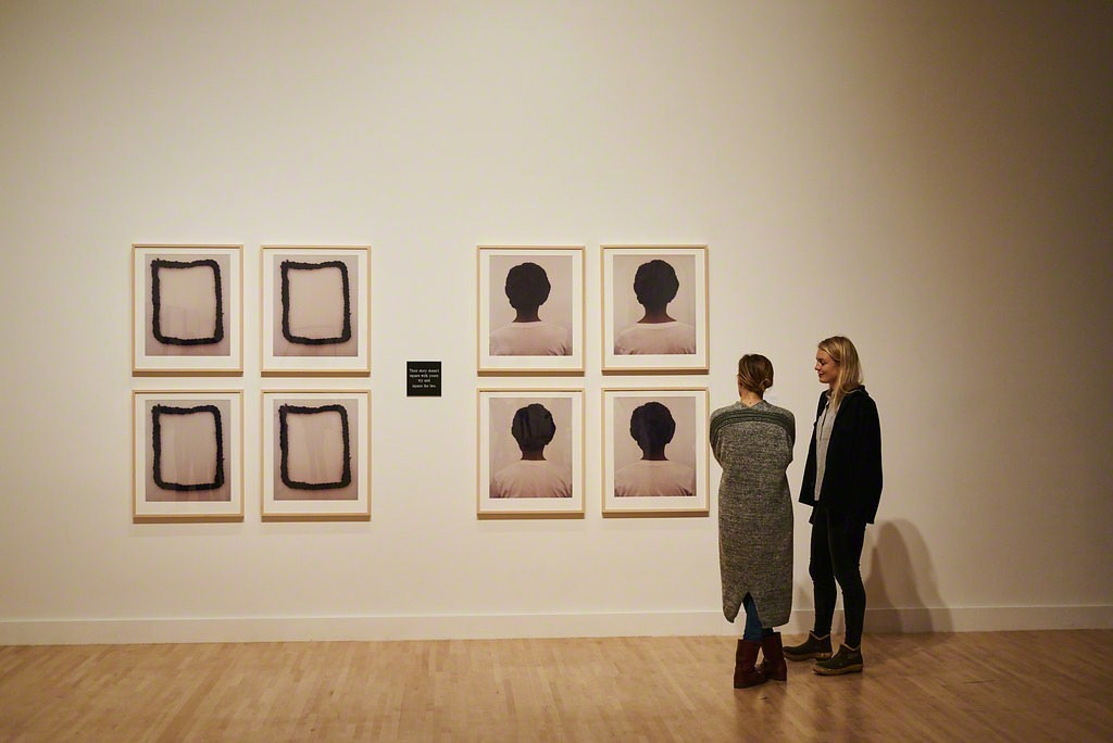 "Guests discussing Lorna Simpson's 1990 work ""Square Deal"" at the Fall 2017 Open House.