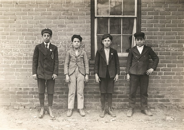 Lewis Wickes Hine, 'Sweepers and mule-room boys in Royal Mill, River Point, R.I. Boy left hand end, Manuel Mites has been in mill 2 years. Clinton Silvey and Louis Perry (centre boys) have been in mill one year and said they are now 12 years old. Boy on right hand Manuel Silvey been in mill 1 year. (They could not speak English.) Location: River Point, Rhode Island.', 1909, San Francisco Museum of Modern Art (SFMOMA)