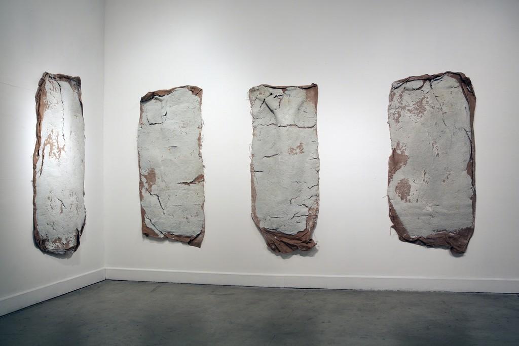"Erika Ostrander, ""Compression (Blue Book)"",  2016, pulped blue books, salt, burlap, racoon tracks"