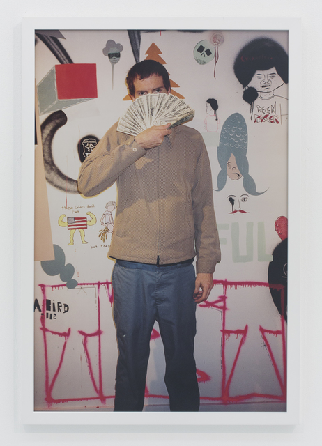 , 'Holding money in front of wall of me and barry's art,' 2002, The Hole