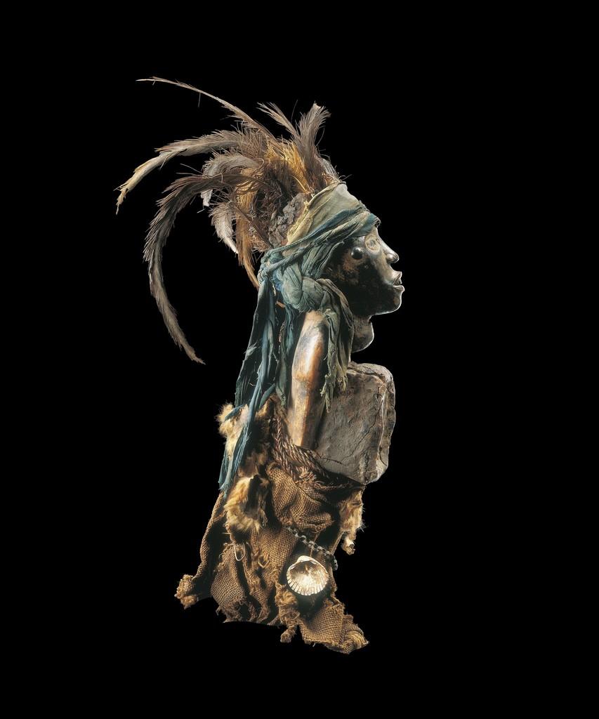 KONGO RÉPUBLIQUE DÉMOCRATIQUE DU CONGO Statuette nkisi Bois, plumes, fibres végétales, matières composites, coquillage, métal, miroir, peau et pigments H.: 38cm Inv.n°0004 Collectée par Robert Visser en 1903. © Archives Musée Dapper - Photo Hughes Dubois.