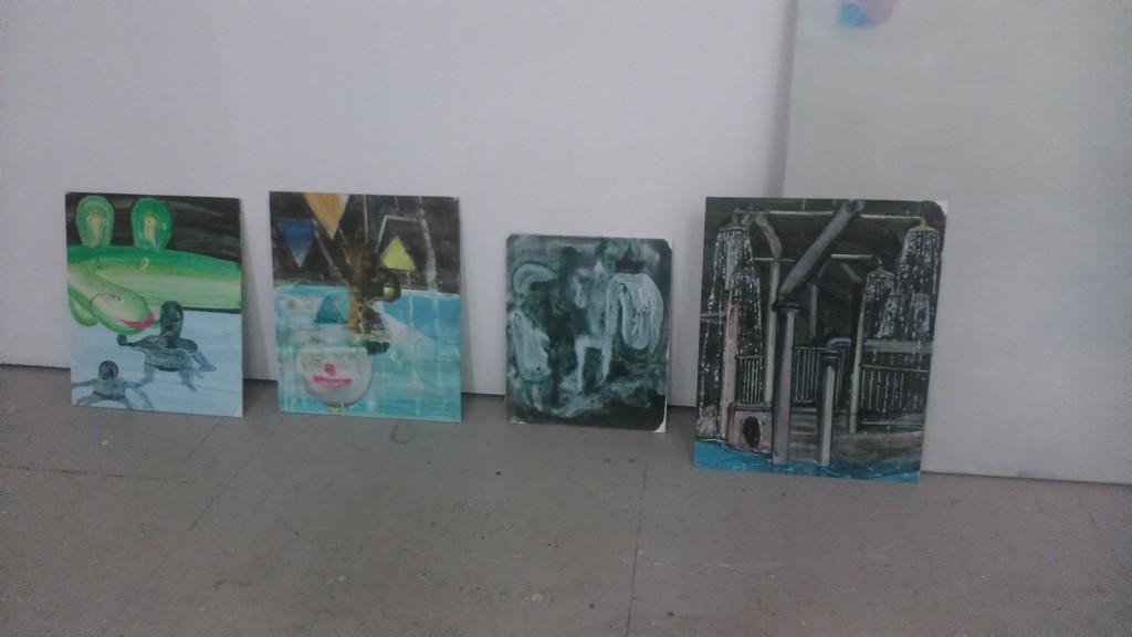 Various paintings on display in the artist's studio.