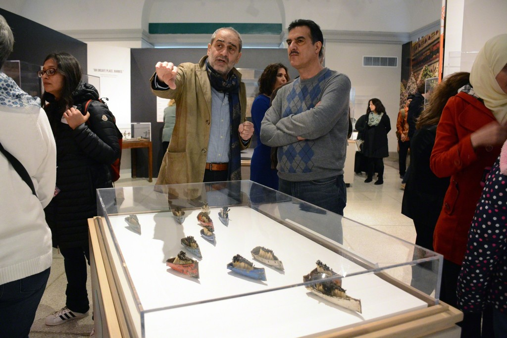 "Syrian artist Issam Kourbaj speaks with a visitor about his ""art intervention"" in the Penn Museum's new exhibition, ""Cultures in the Crossfire: Stories from Syria and Iraq."""