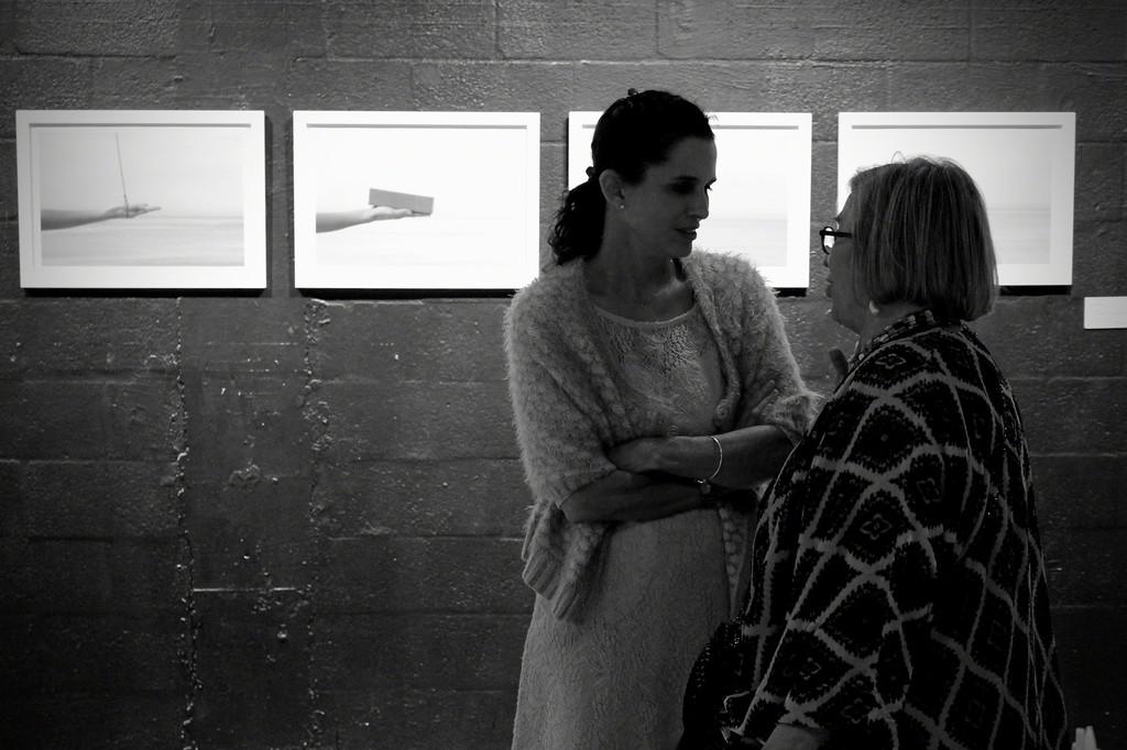"Artist Maritza Caneca with a guest.   Artwork by Bia Monteiro ""Untitled"" 1-4, 2015  Series Vazio Atrás Edition 1/5"