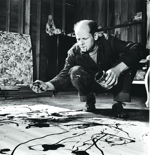 Artist Jackson Pollock Dribbling Sand on Painting While Working in his Studio