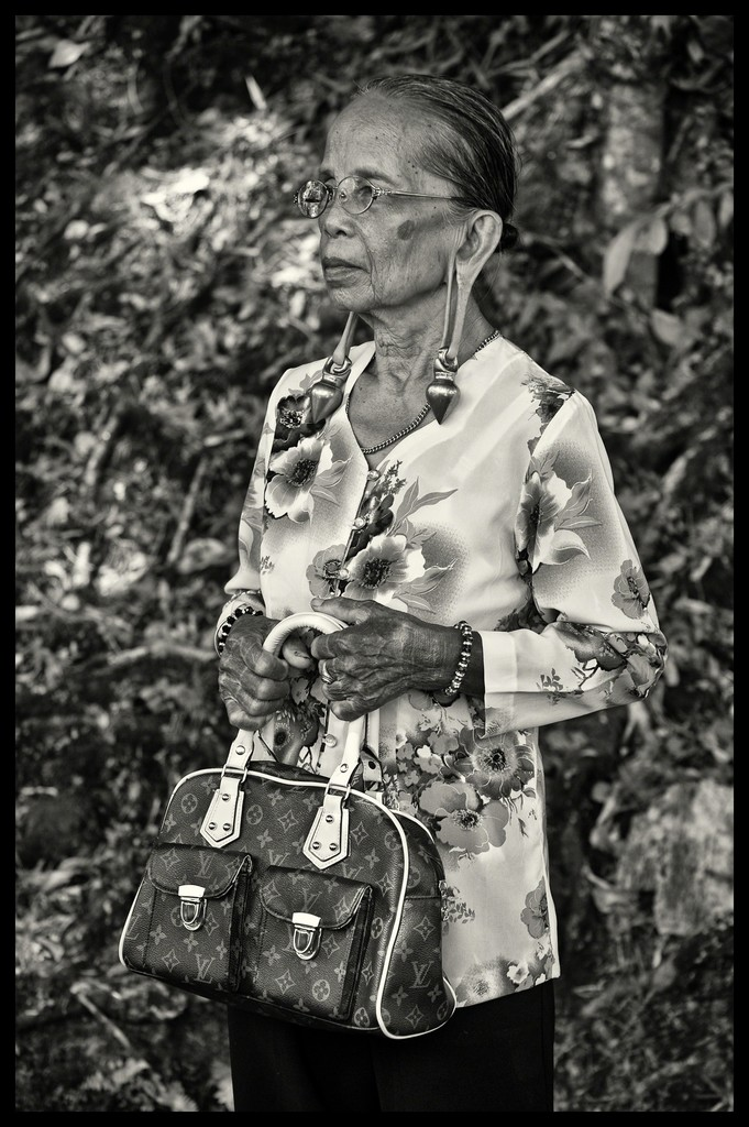 This Kayan women is from Upper Baram River in Long Miri. Her ear lobes are distended by heavy brass rings.  Why is this image important? It epitomizes the idea of change where there is no conflict between traditional values (wearing the brass ear rings) and carrying a modern LV handbag. Her tattooed hands also tell you of her aristocratic background.