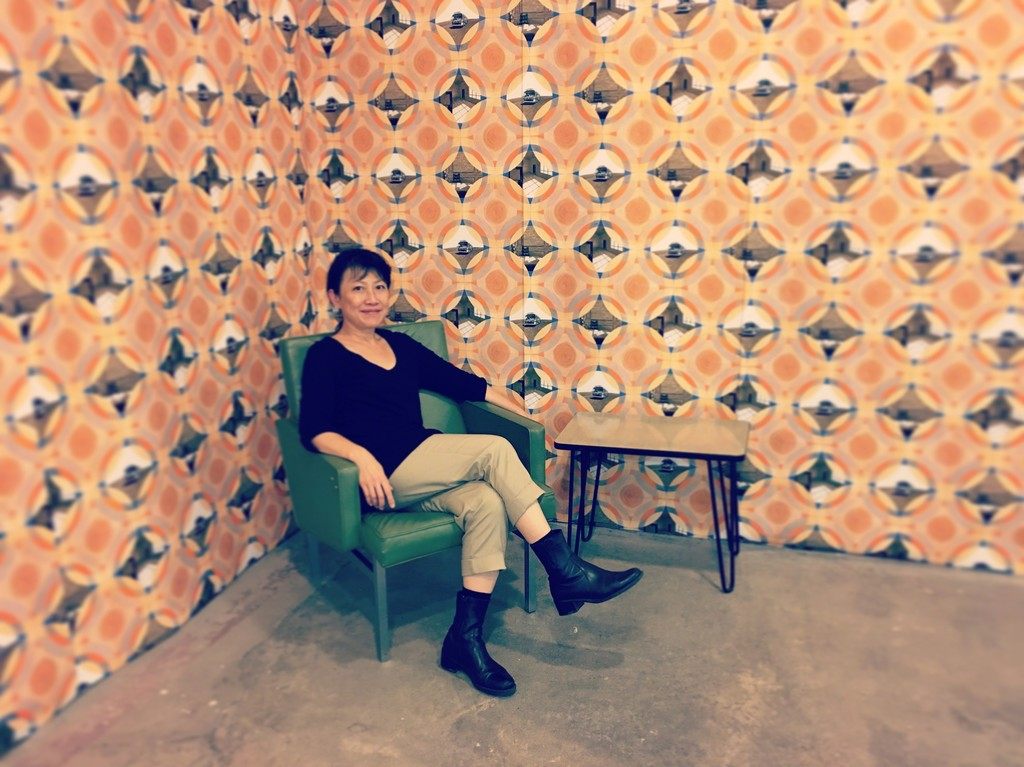 "As part of the exhibition, ""Prototype 1977"" has been mocked up as actual wallpaper, complete with 1970s era furniture. Pictured here is the artist, Millie Chen."