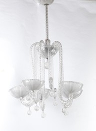 A pendant lamp with a metal structure and Murano glass