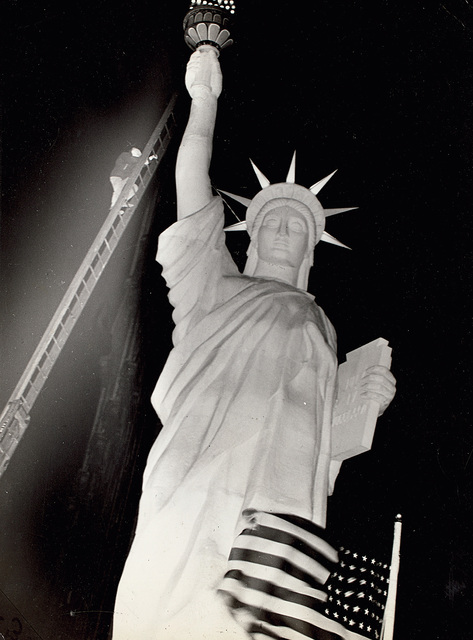 Weegee, 'Man climbs 85-foot ladder to secure torch on the plastic Statue of Liberty erected at Times Square for the Sixth War Loan Drive, New York, November 30', 1944, Phillips