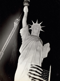 Man climbs 85-foot ladder to secure torch on the plastic Statue of Liberty erected at Times Square for the Sixth War Loan Drive, New York, November 30