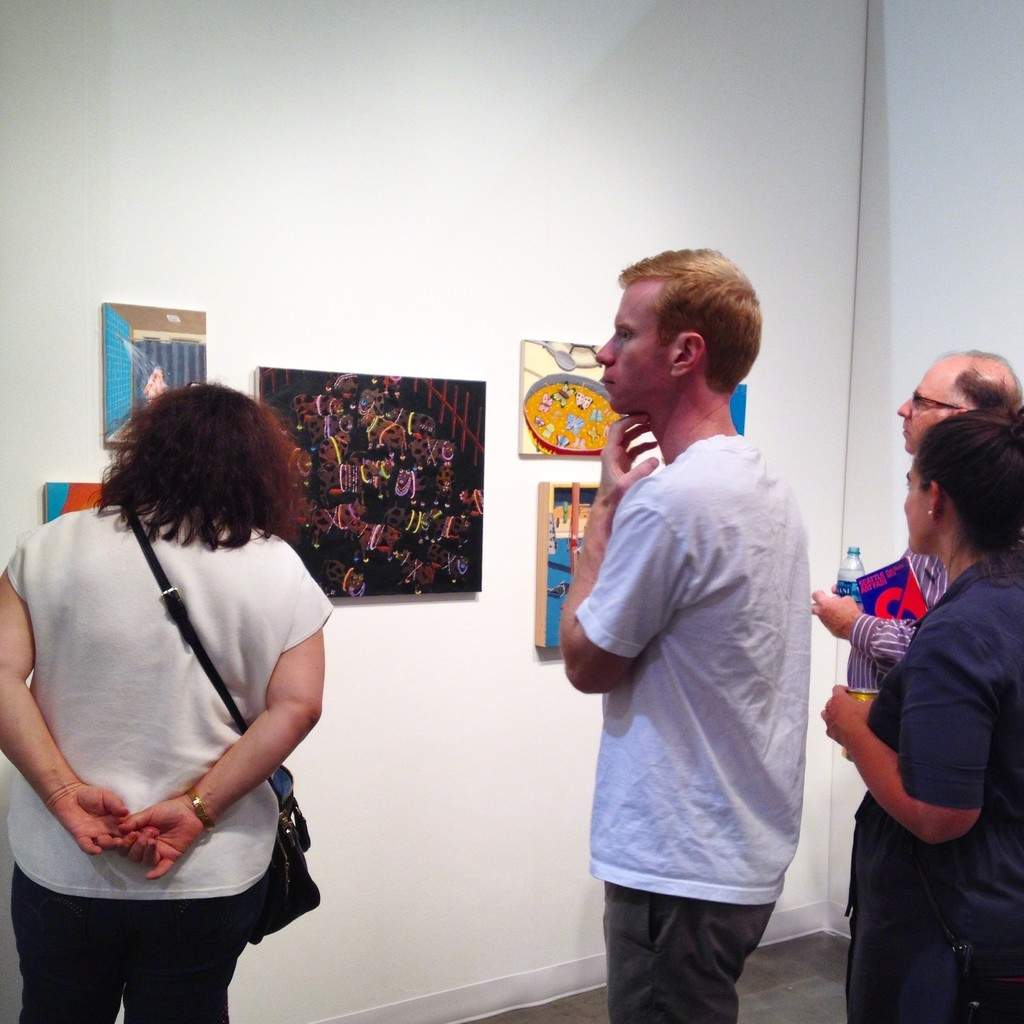 Art fair attendees take in paintings by Ralph Pugay during the Seattle Art Fair.