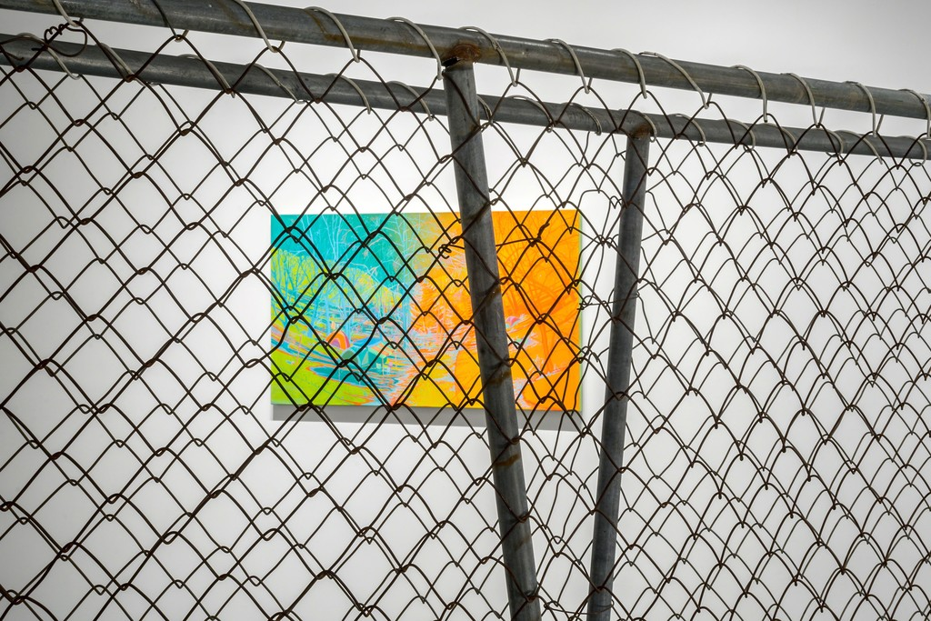 """Camp Jimmy"" seen through a section of chain link fence at PROTO Gallery."