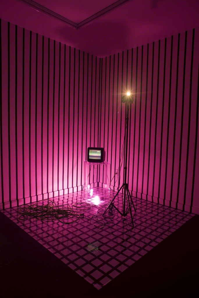"Paula Morales, ""Reciprocity,"" 2017, 1-channel video installation with analog camera feedback loop to CRT monitor, av cables, and pink LED lightbulb, Dimensions variable"