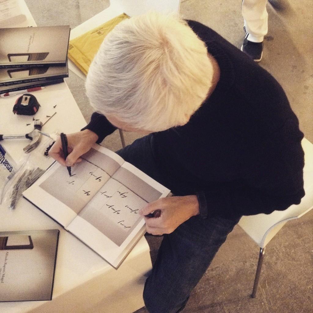 Alfredo Rapetti Mogol signs books.