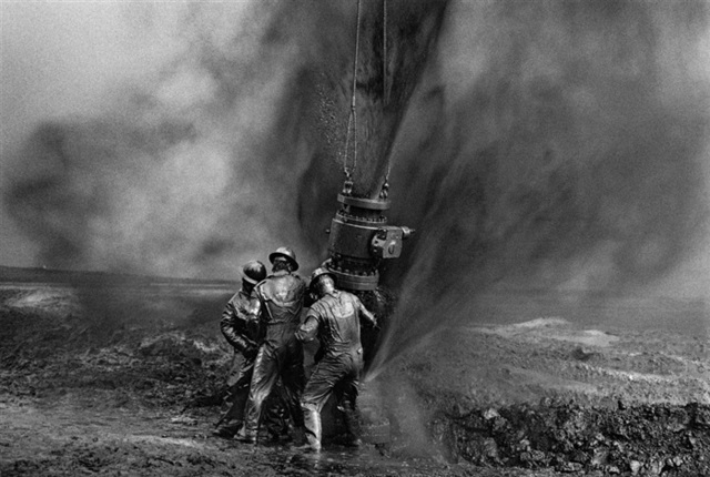 Sebastião Salgado, 'Workers struggle to remove bolts from the remains of an old wellhead. Working with metal tools can produce sparks, threatening to consume everything in flames, Oil Wells, Greater Burhan, Kuwait', 1991, Photography, Silver gelatin print, Galerie Bene Taschen