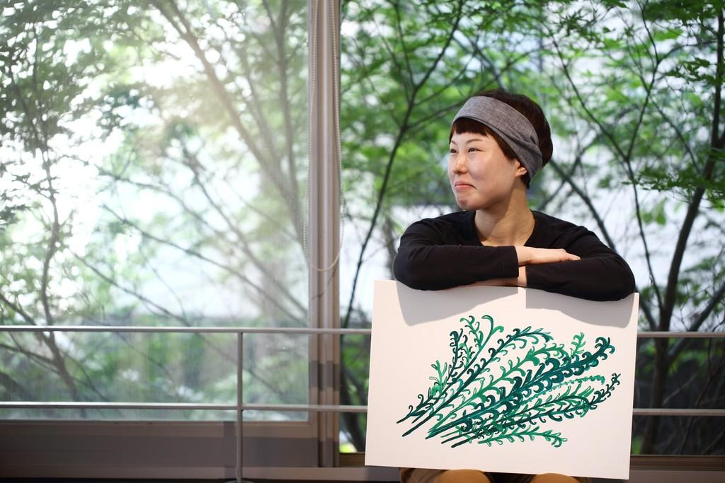 Artist Tomomi Takshio with her work