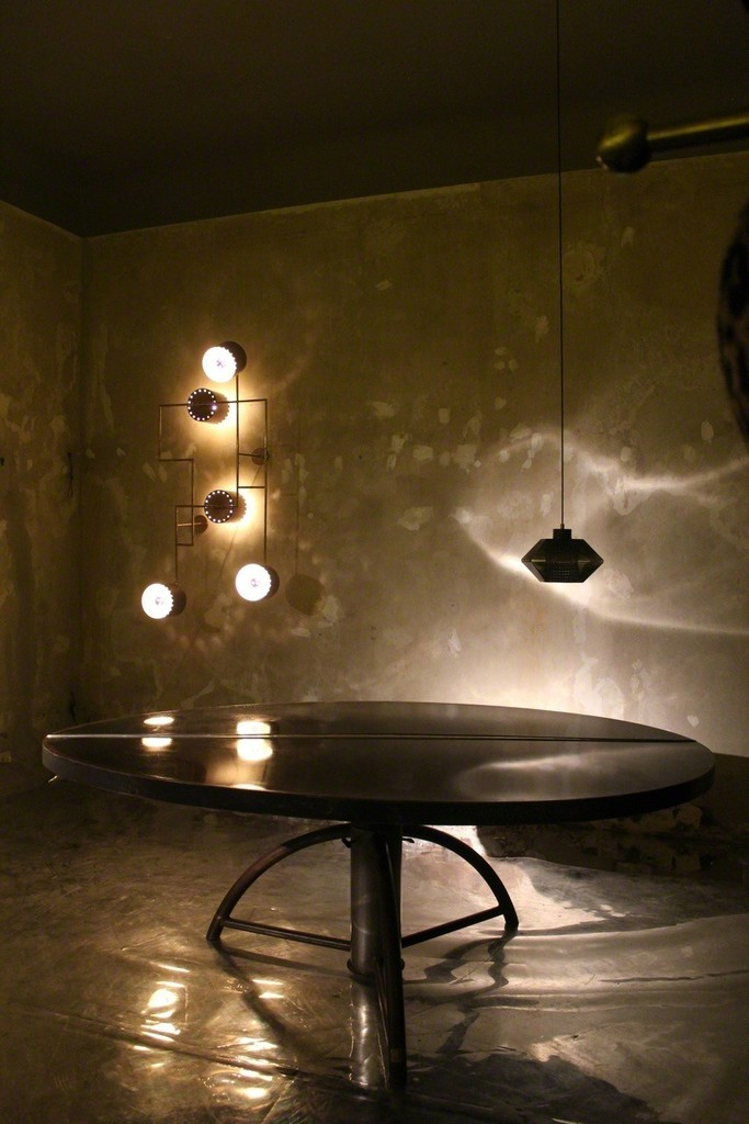 "The organic ""Ovum Aureum"" table expressing the artists expermentation with alchemy is adorned thanks to the juxtaposition of two very geometric lamps"