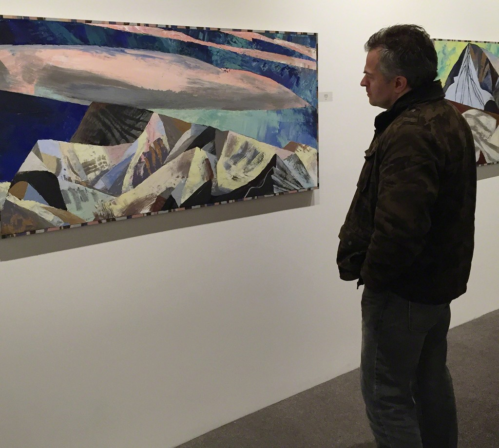 "An unidentified man inspects Lucinda Parker's painting, ""Orogeny"""